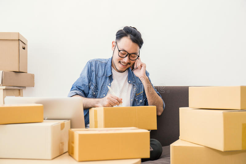 Young man packing and moving their house, online marketing packaging and delivery,. Start up small business entrepreneur or freelance man working at home concept royalty free stock photo