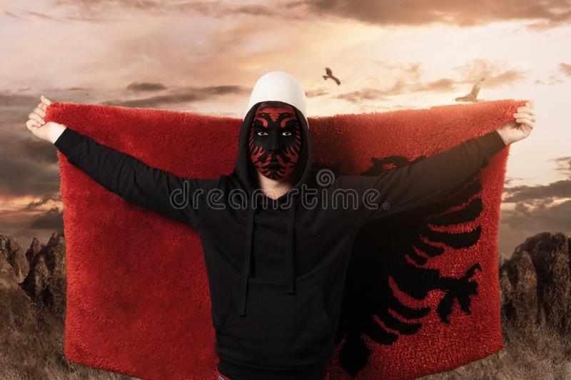 Young man with paintad albanian flag on face standing in front of rocky landscape and flying the fluffy albanian flag.  royalty free stock image