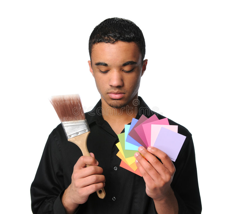 Young Man With Paintbrush and Swatches. Young man with paintbrush and color swatches stock image