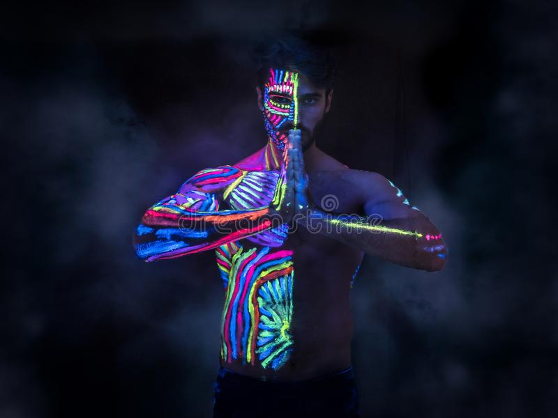 Young man painted in fluorescent paint. On face and muscular torso, in studio shot with UV light royalty free stock photography