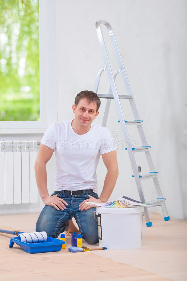 Young man painter sittin on the floor with painting tools and lo stock photos