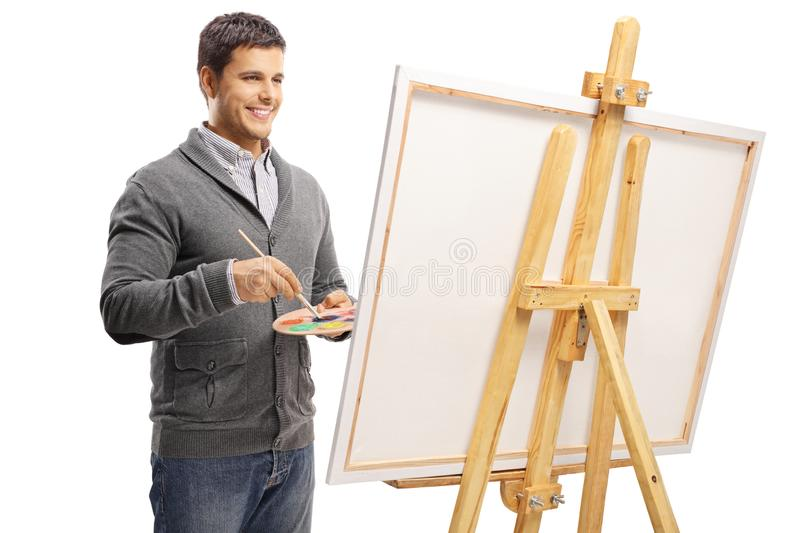 Young man painting on a canvas royalty free stock image