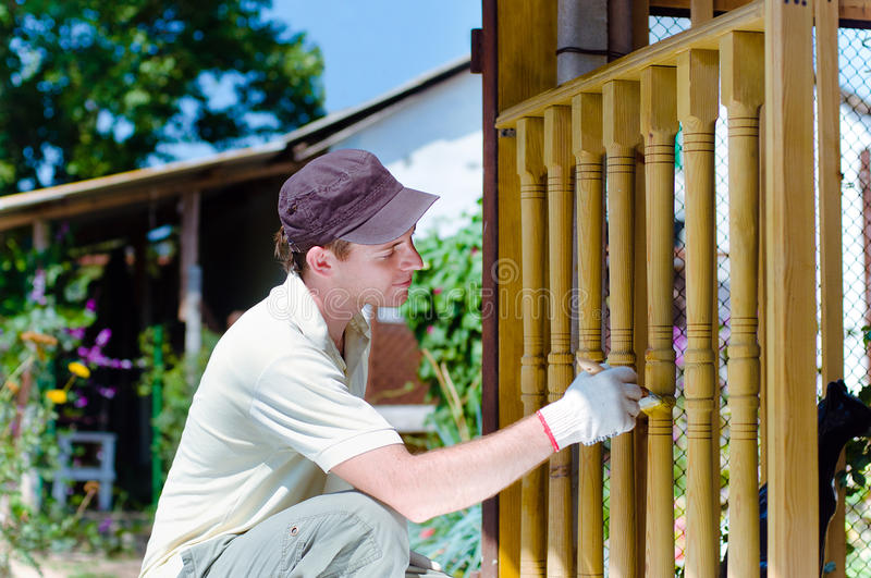 Young man painting wooden fence royalty free stock photography