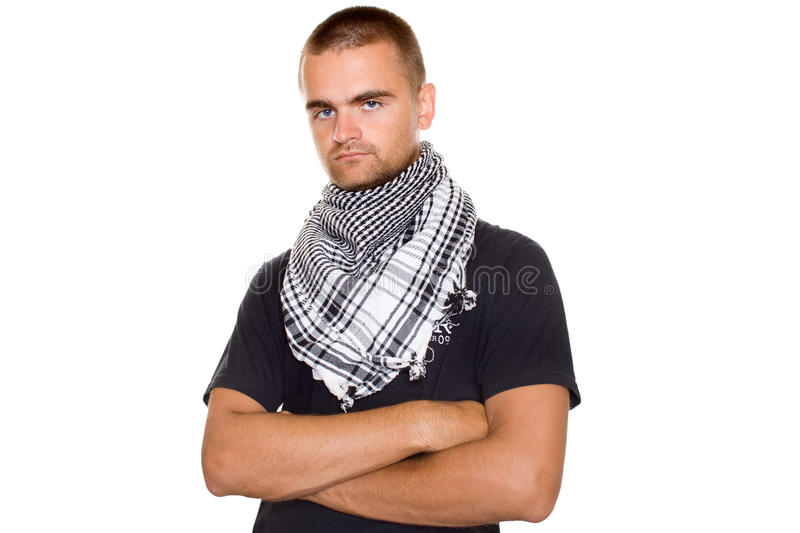 Young man in a Palestinian scarf. Young man dressed in black t-shirt at the neck of a Palestinian scarf. Hands crossed on his chest. Stubble on his face. Lots of royalty free stock photo