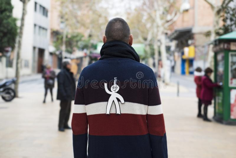 Young man with a paper man attached to his back. Young man in the street with a paper man in his back as a prank for the dia de los inocentes, the innocents day stock photography