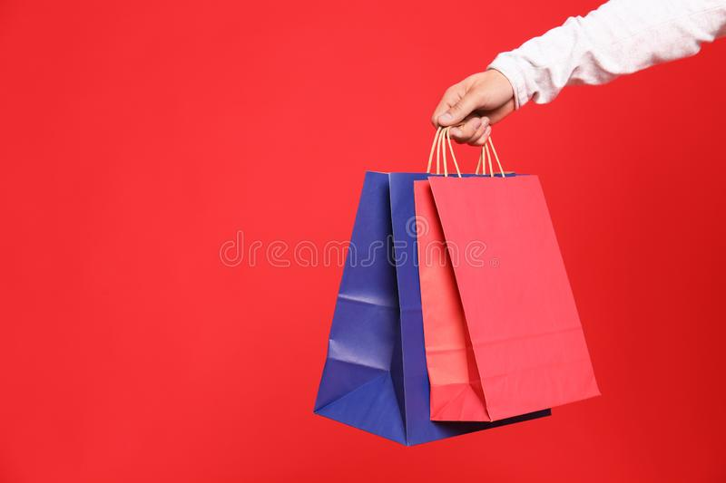 Young man with paper bags on red background, closeup royalty free stock image