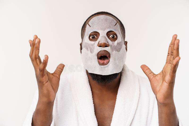 A young man with paper mask on face looking shocked with an open mouth, isolated on a white background. royalty free stock photography