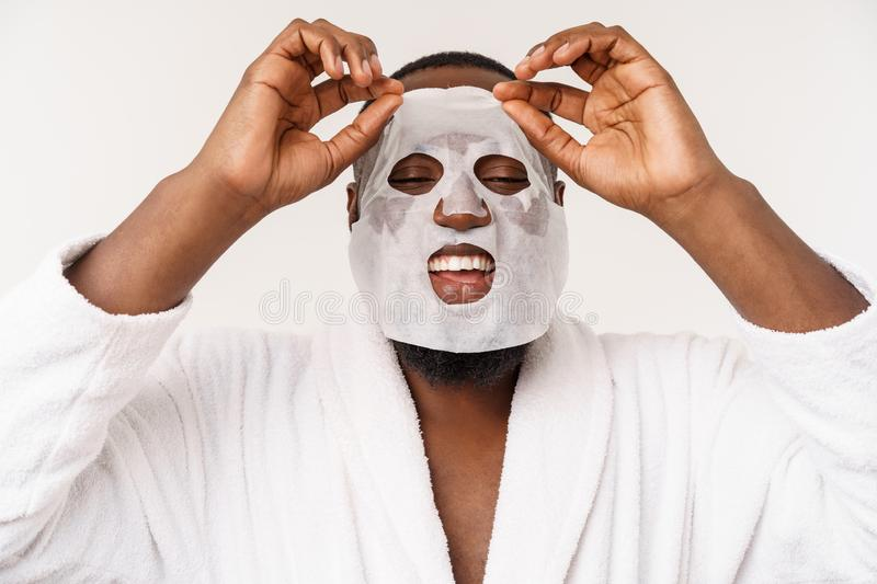 A young man with paper mask on face looking shocked with an open mouth, isolated on a white background. stock photos
