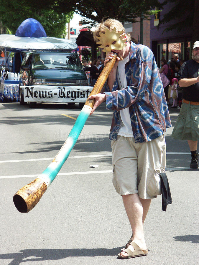 A young man in a parade blowing an Australian horn stock photos