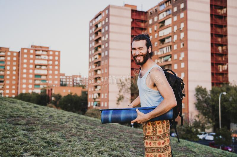 young man in a park ready to practice yoga sport. city background. healthy lifestyle stock images