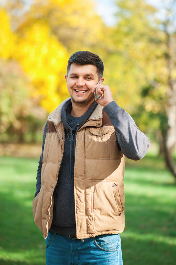 Young man in the park is speaking by phone royalty free stock image