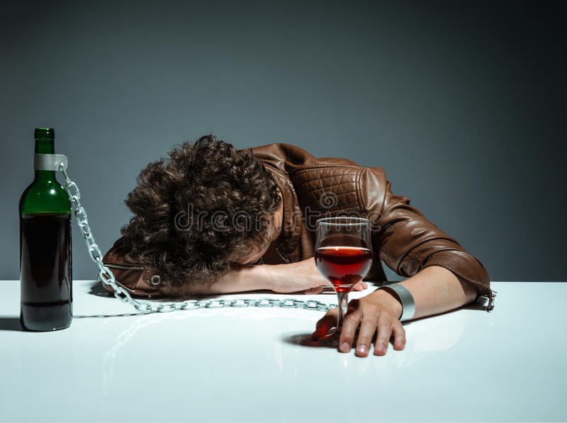 Young man passed out from alcohol. Photo of youth addicted to alcohol, alcoholism concept, social problem stock images
