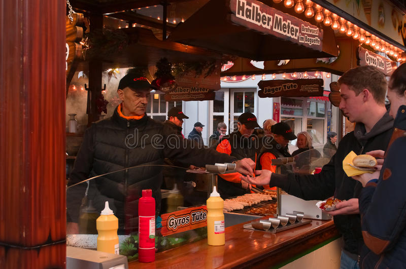 A young man paying on a Christmas market in Goettingen, Germany royalty free stock images