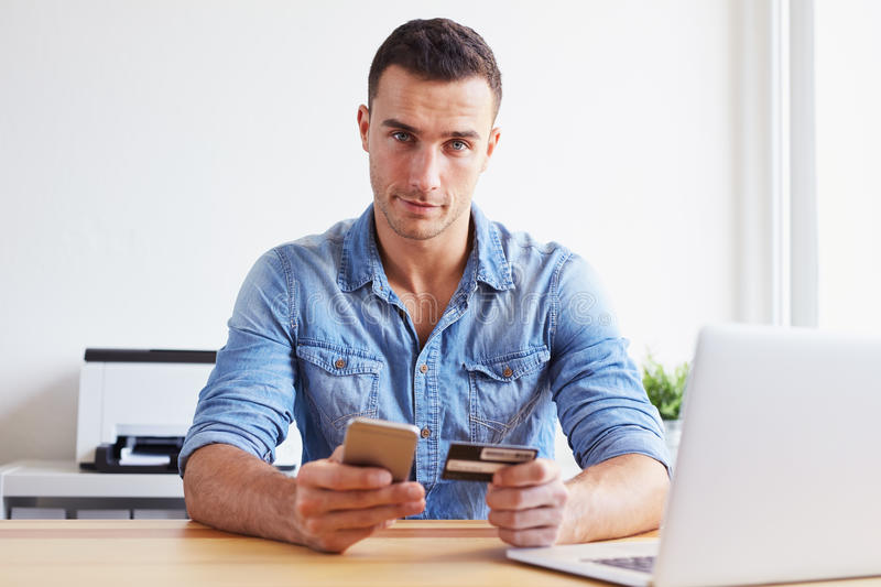 Young man pays by credit card with his mobile phone royalty free stock images