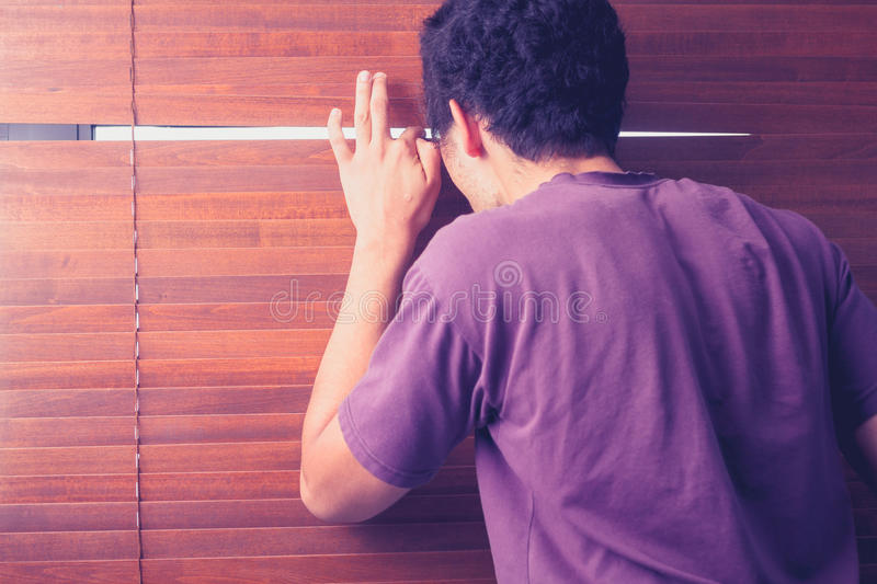 Young man peeping out through venetian blinds. Young man is peeping out through the venetian blinds in his room stock image
