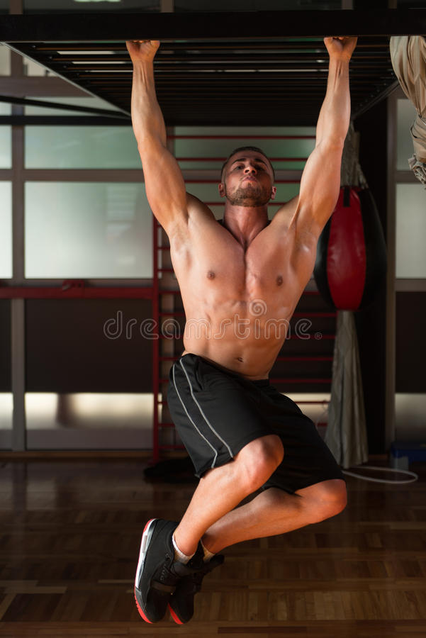 Young Man Performing Hanging Leg Raises Abs Exercise. Young Man Performing Hanging Leg Raises Exercise - One Of The Most Effective Ab Exercises royalty free stock images