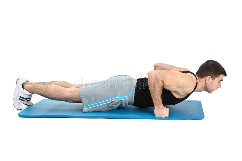 Young man performing push-ups exercise on fists royalty free stock photography