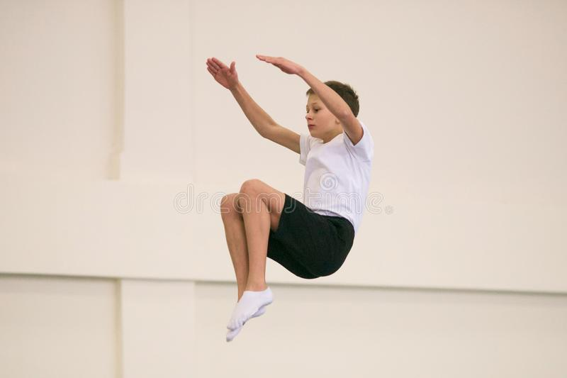 The young man performs gymnastic exercises in the gym. stock image