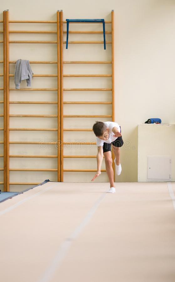 The young man performs gymnastic exercises in the gym. royalty free stock image