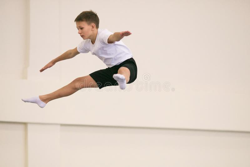 The young man performs gymnastic exercises in the gym. stock photography