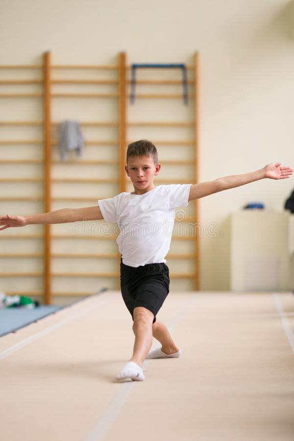 The young man performs gymnastic exercises in the gym. royalty free stock photography