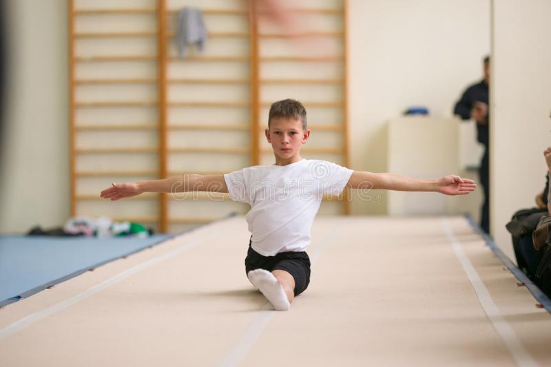 The young man performs gymnastic exercises in the gym. royalty free stock photos
