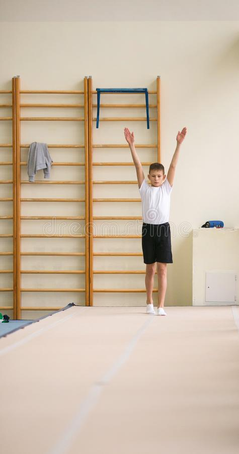 The young man performs gymnastic exercises in the gym. stock images