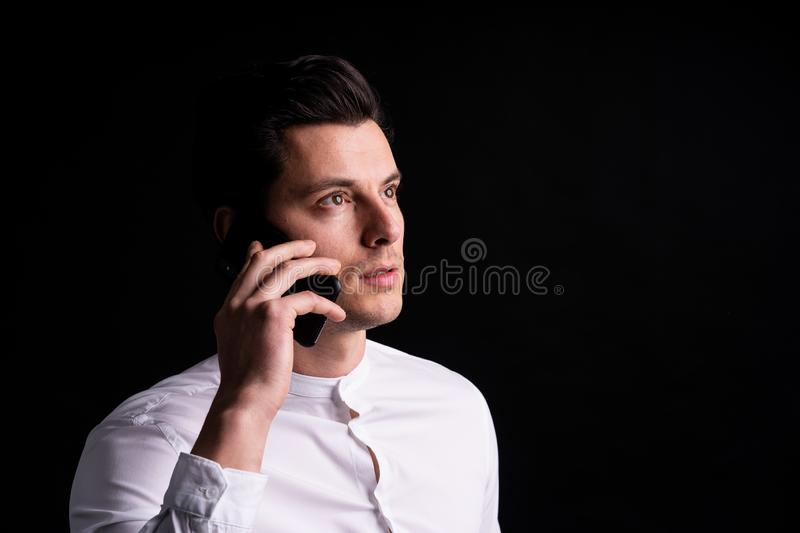 young man with phone in hands look somewehere and thinking stock image