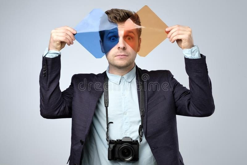 Young man photographer with dslr camera holding color filters. Red and blue in hands stock images