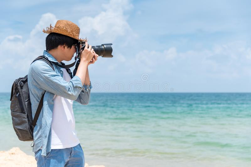 Young man photographer take photos on the beach. Young Asian man photographer with jean shirt and hat take photo of tropical island beach and turquoise sea stock image