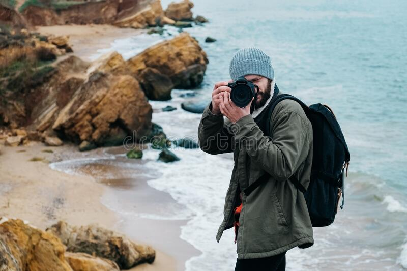 Young man photographer traveler with backpack taking pictures on sea and rocks background. Place for text or advertising.  royalty free stock photography