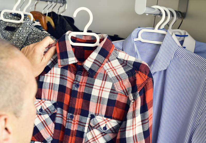 Young man picking a shirt from the closet stock images