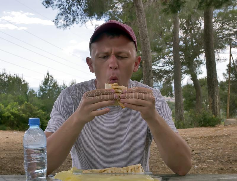 Young attractive man on a picnic eating shawarma sitting at a wooden table, eating in nature, fast food royalty free stock images