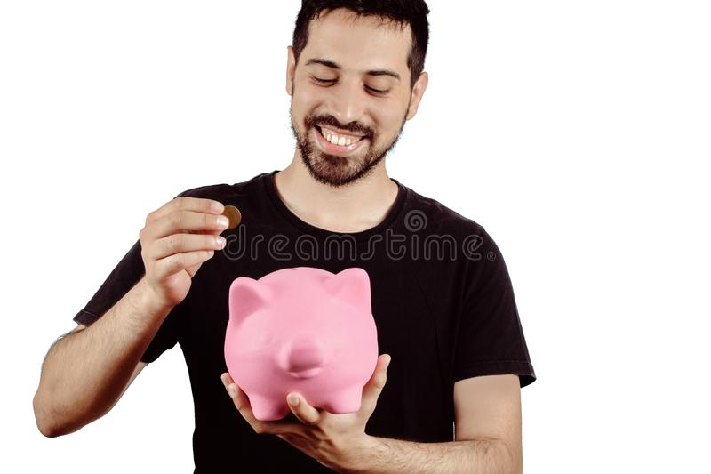 Young man with piggy bank. Portrait of young man putting a coin in a piggy bank on studio. Save money concept stock photos