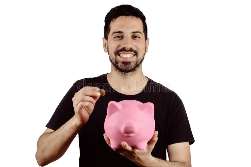 Young man with piggy bank. Portrait of young man putting a coin in a piggy bank on studio. Save money concept royalty free stock photography