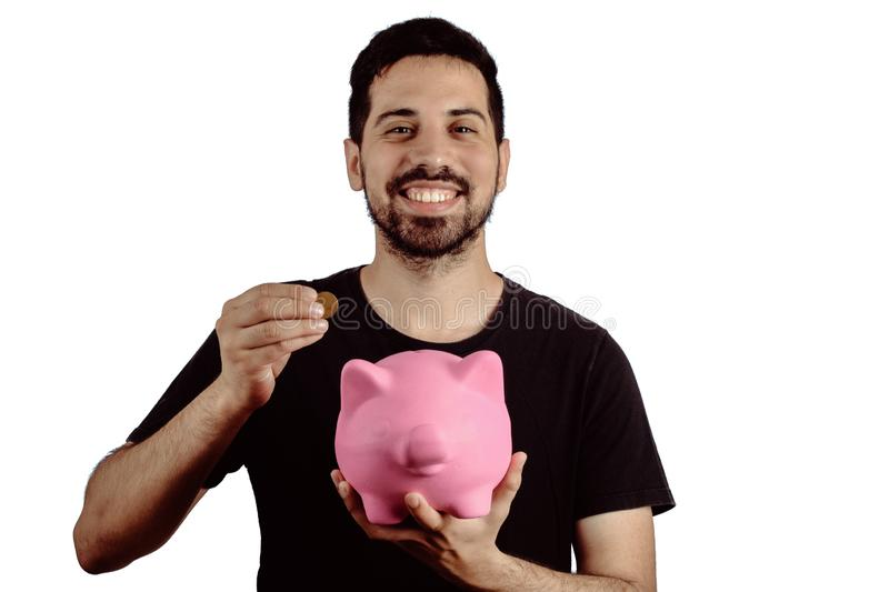 Young man with piggy bank. Portrait of young man putting a coin in a piggy bank on studio. Save money concept royalty free stock photo