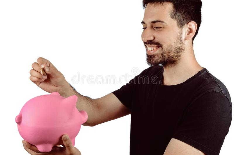 Young man with piggy bank. Portrait of young man putting a coin in a piggy bank on studio. Save money concept stock image