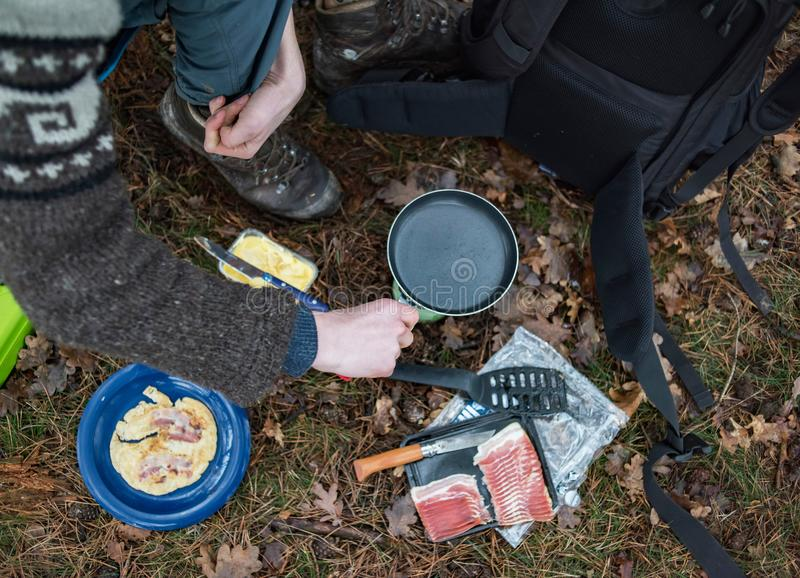 Young man placing fry pan on gas burner on campsite. Top view royalty free stock image