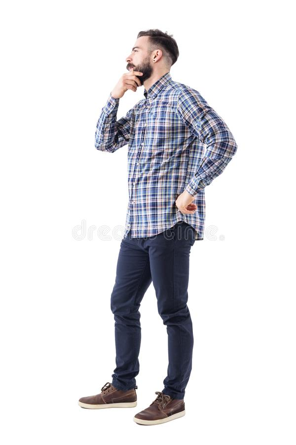 Young man in plaid shirt holding beard thinking and looking away. Side view. royalty free stock photography