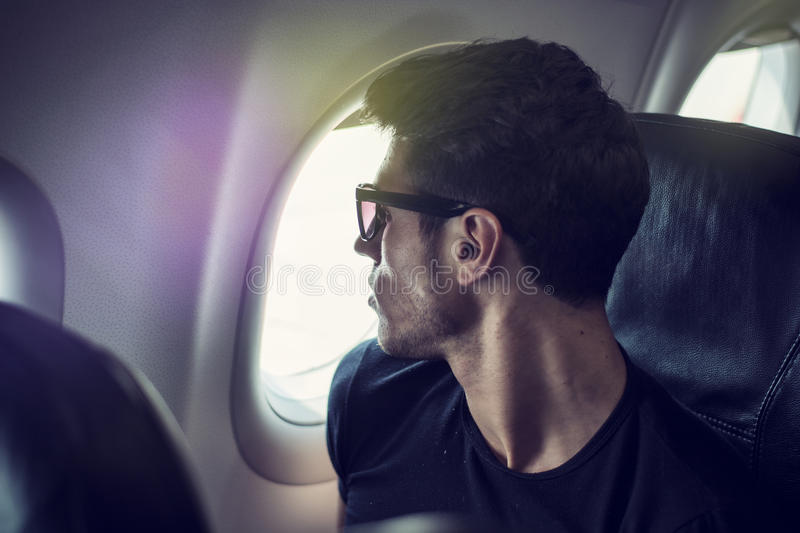 Young man in plane. Side view of handsome young man against plane window sitting and looking out royalty free stock photo