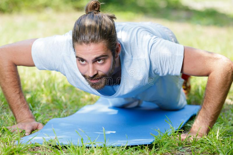 Young man in plank position exercising outdoors. Man stock photos