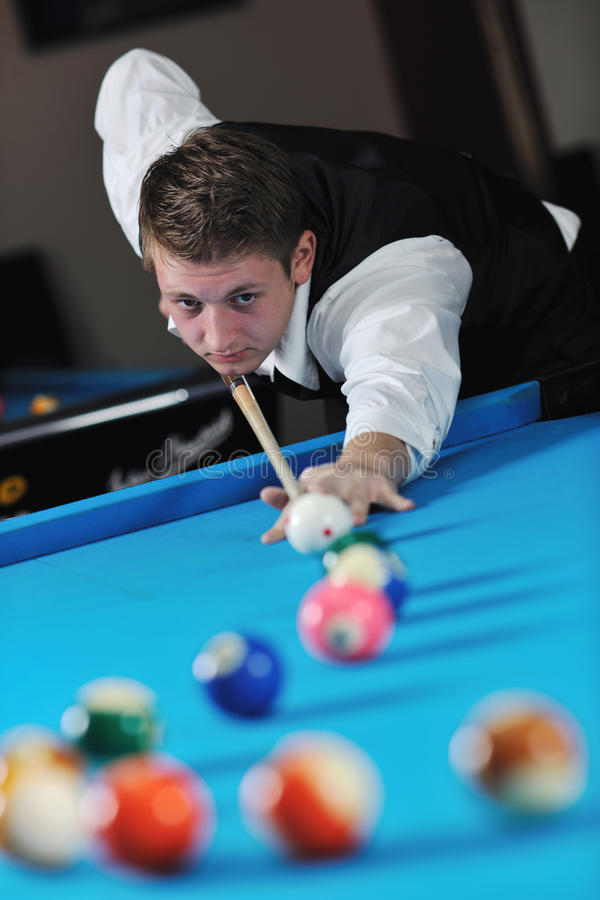 Young man play pro billiard game. Young pro billiard player finding best solution and right angle at billard or snooker pool sport game royalty free stock photography