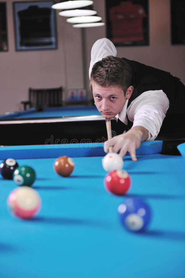 Young man play pro billiard game. Young pro billiard player finding best solution and right angle at billard or snooker pool sport game stock photo