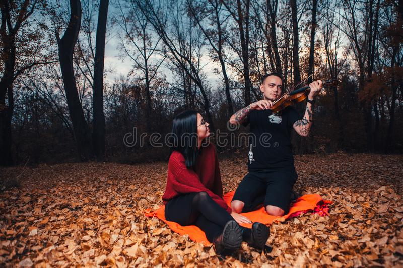 Young man play on violin and young woman are sitting on a plaid in an autumn forest royalty free stock images