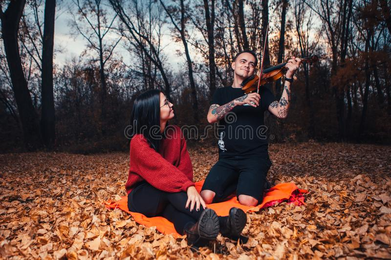 Young man play on violin and young woman are sitting on a plaid in an autumn forest royalty free stock image