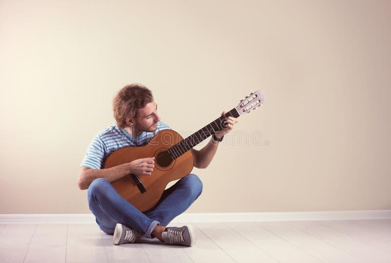 Young man playing acoustic guitar near grey wall. stock photos