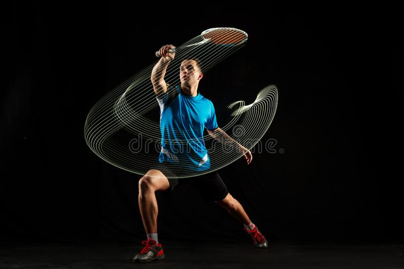 Young male badminton player over balck background. Young man playing badminton over black studio background. Fit male athlete isolated on dark with led light stock photography