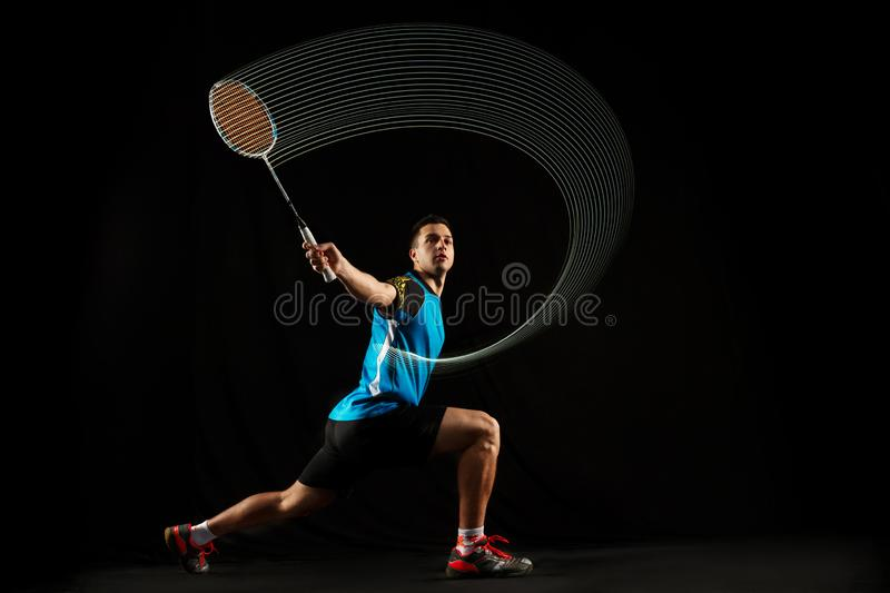 Young male badminton player over balck background. Young man playing badminton over black studio background. Fit male athlete isolated on dark with led light stock images