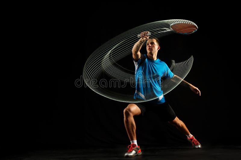 Young male badminton player over balck background. Young man playing badminton over black studio background. Fit male athlete isolated on dark with led light royalty free stock photo