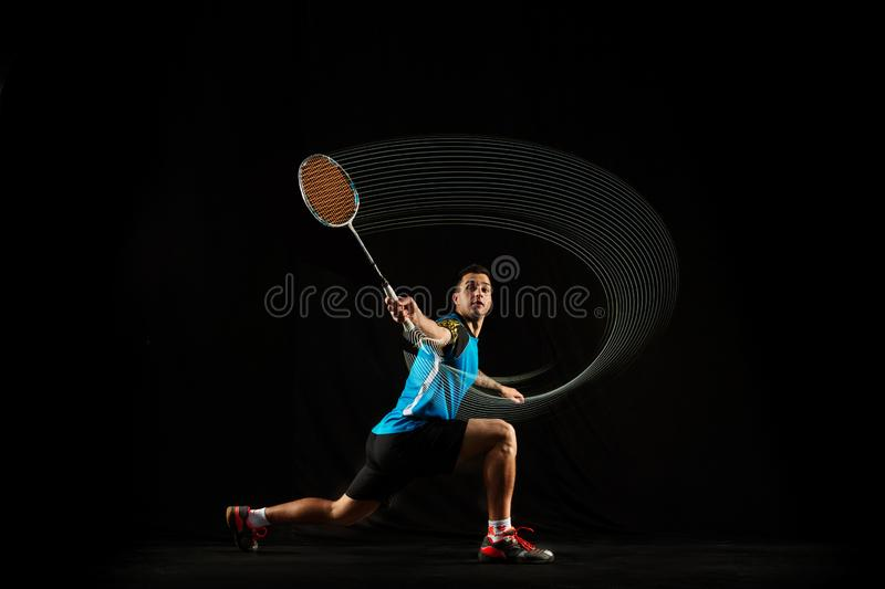 Young male badminton player over balck background. Young man playing badminton over black studio background. Fit male athlete isolated on dark with led light royalty free stock image